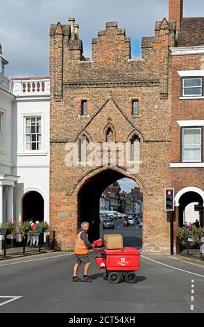 Postman with trolley, delivering the mail, North Bar in Beverley, East Yorkshire, England UK - Stock Photo