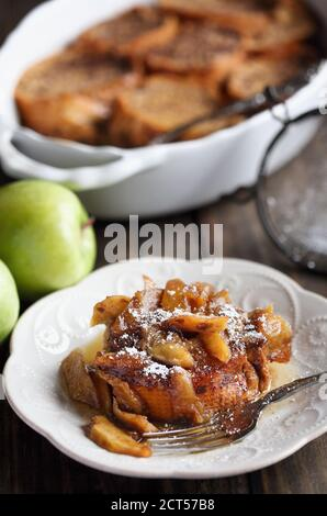 Serving of apple French toast casserole with maple syrup and powdered sugar. Selective focus with blurred background. - Stock Photo