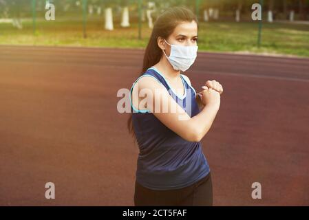 A young woman goes in for sports on the street in a protective mask. Sport during quarantine, coronavirus, covid-19 concept. Stock Photo