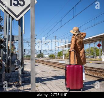 Back view of anonymous woman with suitcase waving hand with hat and walking on platform of railroad station during summer vacation