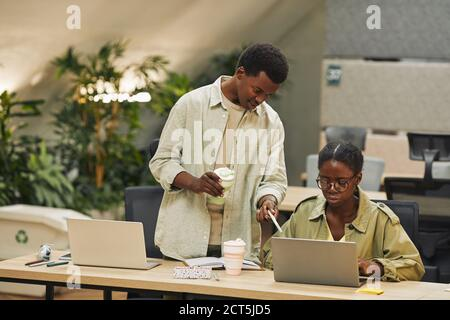 Portrait of two African-American people working in modern open space office, focus on young man instructing colleague and pointing at laptop screen , copy space