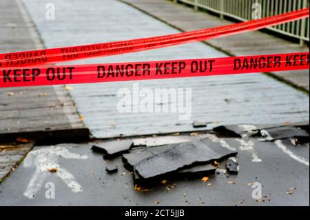Red tape reading 'danger keep out' preventing people crossing a bridge. Taken in Christchurch after the earthquake which struck on 22nd February 2011. - Stock Photo