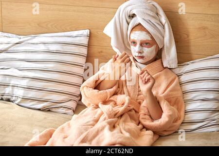 sweet caucasian kid girl in mask relax on weekends, leisure time. little girl saws nails with a file, take care of herself, natural beauty concept - Stock Photo