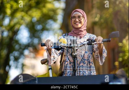 Confident Muslim woman using cargo bike in urban area - Stock Photo