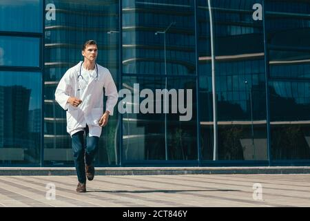 in full growth. a concerned doctor runs to help. Stock Photo