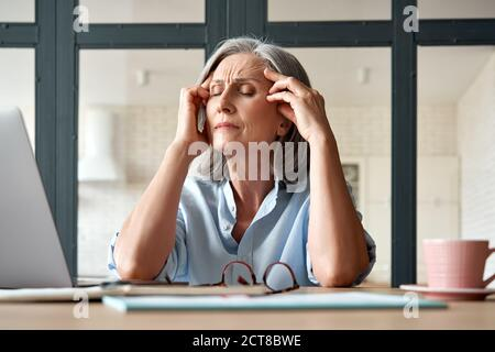 Tired stressed old mature business woman suffering from headache at work.