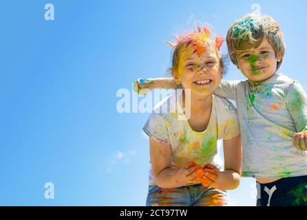 Two kids with face smeared with colors