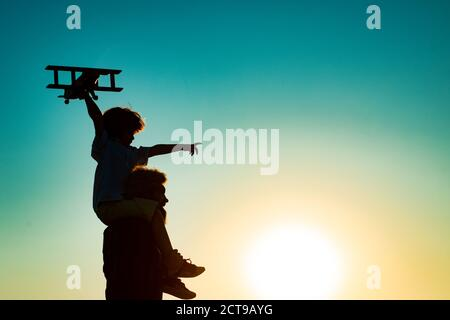 Sunset silhouette of Father carrying his son on shoulders. Child son pilot and dad daddy father with airplane.