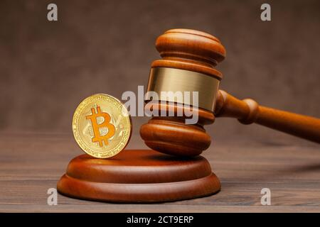 Bitcoin and judge gavel on wooden brown background. - Stock Photo