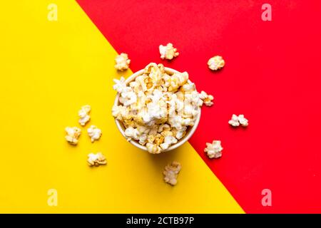 Popcorn in red and white cardboard box on red and yellow background Top view Flat lay Copy space