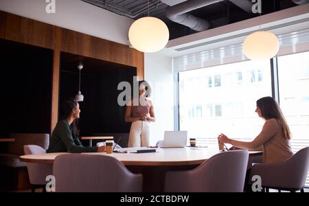 Three Businesswomen Having Socially Distanced Meeting In Office During Health Pandemic