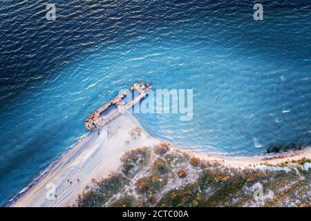 Old shipwreck reinforced concrete barge abandoned stand on beach on the coast of Black sea in Ukraine - Stock Photo