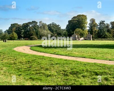 Curved drive leading to lodge houses and bridge over the River Nidd listed buildings in Ribston Park Little Ribston North Yorkshire England - Stock Photo