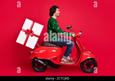 Profile side view portrait of attractive cheerful guy riding moped delivering bringing big large giftbox December bonus St Nicholas tradition isolated - Stock Photo