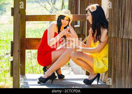 Two teengirls country-girls countrygirls squatting squat on porch entrance of wooden house in countryside country-side small white flower legs heels - Stock Photo