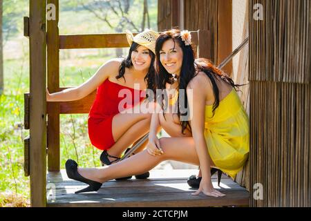 Two teengirls country-girls countrygirls squatting squat on porch entrance wooden house in countryside country-side posing pose for camera legs heels - Stock Photo