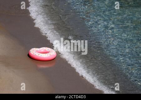 Inflatable ring in donut shape on a sand in sea waves, aerial view. Background for beach vacation, relax and leisure in clean water - Stock Photo