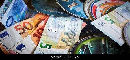 Berlin, Germany - September 10, 2020: Many different discs of computer games mixed with Euro bank notes. - Stock Photo
