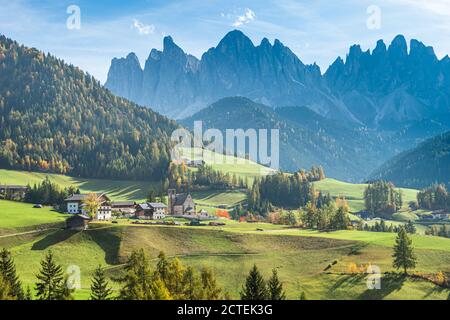 Landscape of early autumn on the church Santa Magdalena in northern Italy on the slopes of the Dolomites in the valley of Val di Funes.