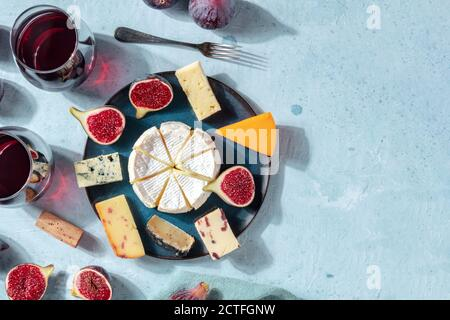 Cheese banner. A variety of cheeses on a plate, shot from the top with a place for text, a flat lay - Stock Photo