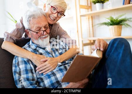 Mature couple relaxing at home and reading book together