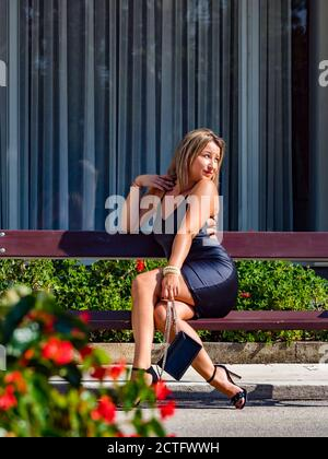 Young woman is sitting on wooden bench expecting for someone waiting wait looking away hoping hope aside hand hold holding purse legs heels - Stock Photo