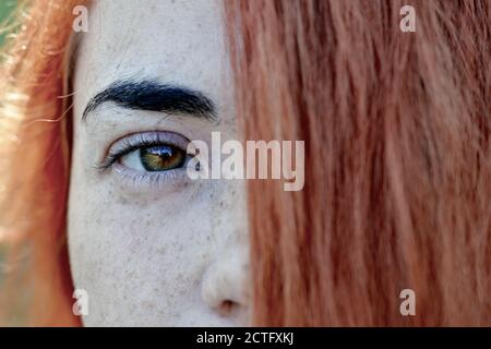 Close up portrait of a red hair woman girl with freckles. Portrait of a girl outdoors in sunlight. Hair covers half of the face.