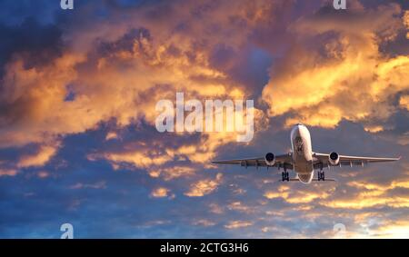 Passenger airplane is flying in colorful sky at sunset