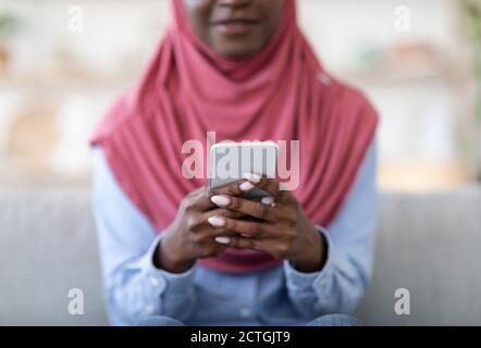 Useful App. Unrecognizable black muslim lady using modern smartphone at home, closeup
