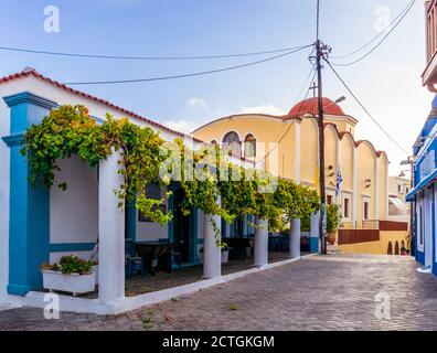 Pigadia, Karpathos, Greece - October 4, 2019: Early morning shot of quiet Apodimon Karpathion street in Pigadia town with church and restaurant