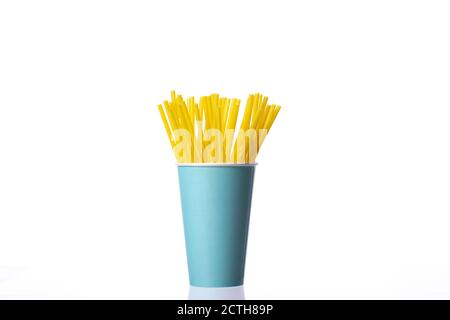Yellow plastic straws in blue disposable paper cup isolated on white background