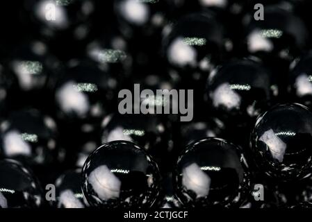 Metal balls with shiny reflections. The balls are arranged next to each other, the structure is made of many elements. Slingshot bullets, ball bearing