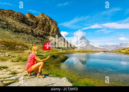 Woman with Swiss flag at Mount Matterhorn or Monte Cervino or Mont Cervin, reflected on Riffelsee Lake. Tourism in Zermatt,Canton of Valais - Stock Photo
