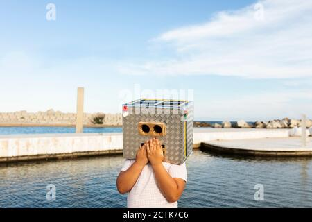 Boy with hands on mouth of robot mask standing by the water against sky - Stock Photo