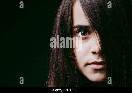 Close-up of girl with long brown hair on face against black background Stock Photo