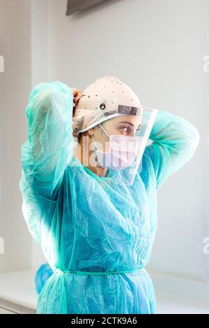 Doctor in protective suit wearing face shield while standing at clinic - Stock Photo