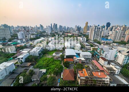 Thailand, Bangkok, Aerial view of residential district with downtown skyscrapers in background
