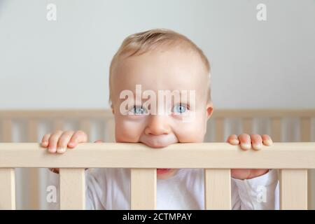 Blond cute little baby biting wooden bed headboard