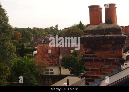 A view level with a traditional brick, four chimney pot stack house roof, showing the lead flashing, cracks in the brickwork and view to other houses - Stock Photo