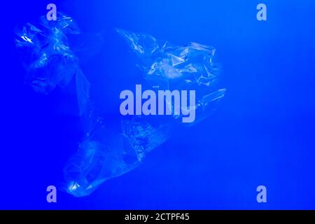 Transparent plastic bags floating underwater in blue ocean sea water, pollution by non-biodegradable plastic waste, hazard for marine wildlife Stock Photo