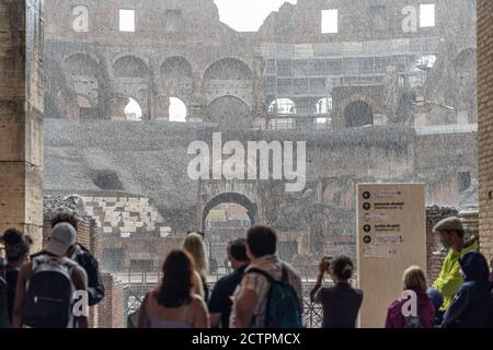Rome, Italy. 24th September, 2020. Italy Weather: Tourists shelter from heavy rain in the Roman Colloseum in Rome, Italy. Photo: Roger Garfield/Alamy Live News - Stock Photo