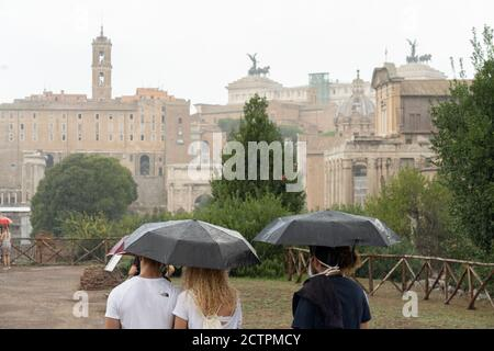 Rome, Italy. 24th September, 2020. Italy Weather: Tourists shelter from heavy rain in the Roman Forum in Rome, Italy. Photo: Roger Garfield/Alamy Live News - Stock Photo