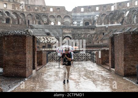 Rome, Italy. 24th September, 2020. Italy Weather: A woman shelters from heavy rain under an umbrella in the Roman Colloseum in Rome, Italy. Photo: Roger Garfield/Alamy Live News - Stock Photo