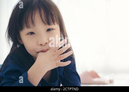 Asian kid cute girll sucking the finger her thumb Stock Photo