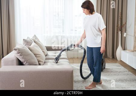 young woman in white shirt and jeans cleaning carpet under sofa with vacuum cleaner in living room, copy space. Housework, cleanig and chores concept - Stock Photo
