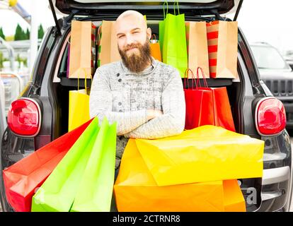Smiling man having fun with lots of bags on a shopping day for the black friday. Concept about how fun is to buy things on these promotional days.