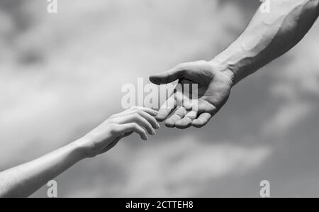 Giving a helping hand. Hands of man and woman on blue sky background. Lending a helping hand. Solidarity, compassion, and charity, rescue. Black and