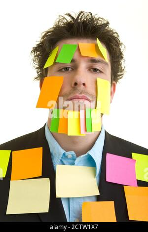 Young man in suit with lots of sticky notes on his face and body - Stock Photo