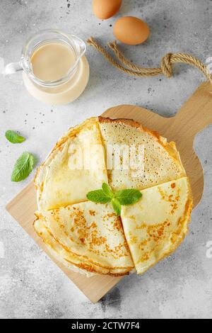 Russian pancakes served with mint leaves and ingredients - milk and eggs in front of grey background. Flat lay composition. Food photography - Stock Photo