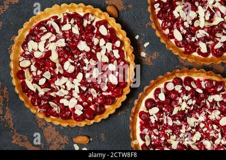 Beautiful freshly made cherry tart decorated with almond chips. Stunning cherry pie flat lay composition. Food photography. Process of making tart.